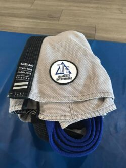 """A gray Gi is folded on the edge of the mats with a blue belt rolled up inside. A patch on the Gi reads """"Triangles Everywhere"""
